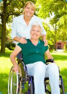 disabled senior woman in wheelchair with her caregiver