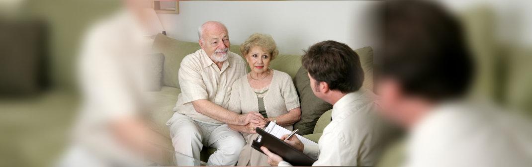 elderly couple talking to staff