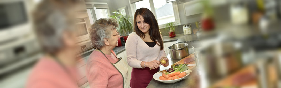 caregiver cooking dinner for her patient