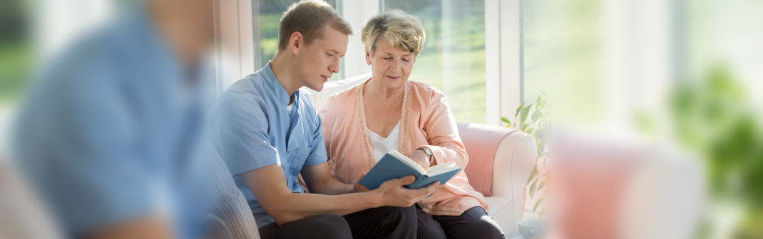 caregiver read a book to her patient